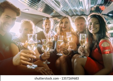 Group of party people in a limo drinking looking at the camera