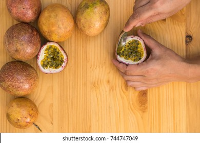 group of passion fruit and hand holding spoon for scoop overhead view