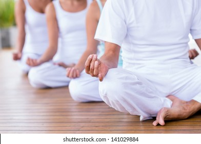 Group of peaceful people meditating  in a yoga studio