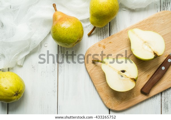 Group of Pears and pieces of pear on a cutting board on white wooden planks with textile napkin, top view