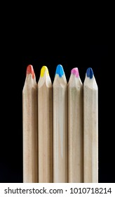 A group of pencil crayons against a black background.