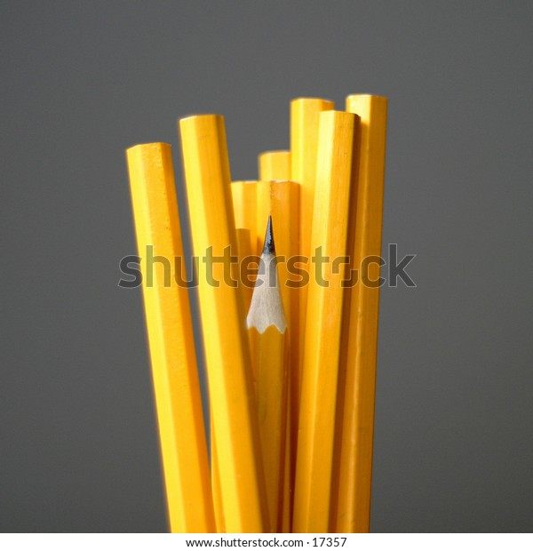 A group of pencils crowding a sharpened pencil which is a little bit lower.