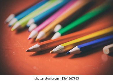 Group of pencils lined up in a red table used by a kid to draw with an old look