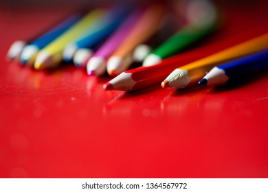 Group of pencils lined up in a red table used by a kid to draw