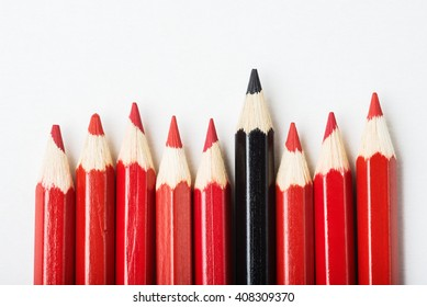 Group of pencils with one black among of red, individuality concept