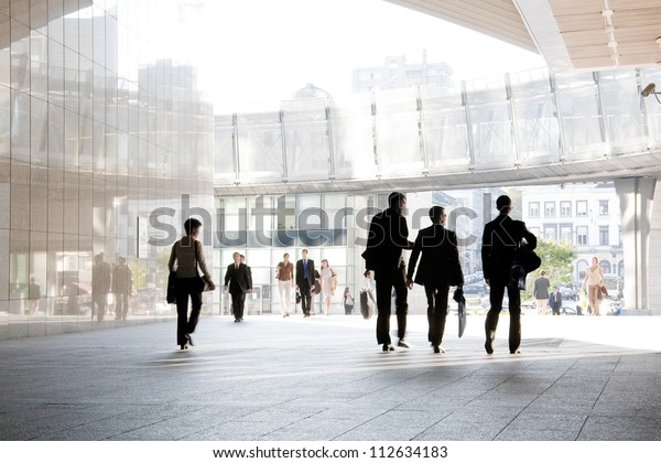 A group of people is against the backdrop of modern buildings. Blurred motion. Silhouette.
