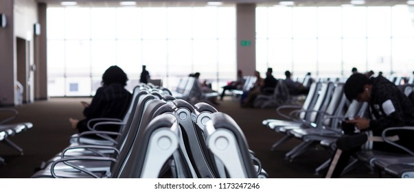 Group of People in airport terminal waiting area with chairs .