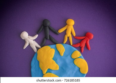 Group of people around the world. People and Earth are made out of play clay (plasticine).