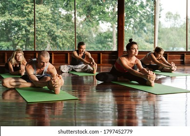 A group of people attending a yoga class in a tropical environment of a yoga meditation retreat