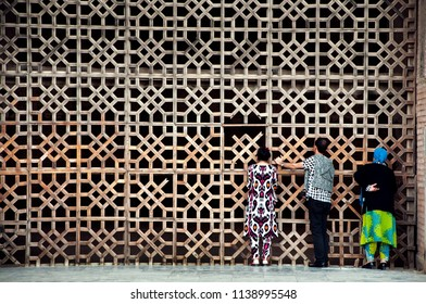 Group of people from the back in traditional uzbek clothes, standing at the wooden decorative gate of Bibi-Khanym Mosque, Samarkand, Uzbekistan