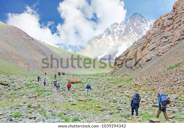 A group of people with backpack trekking to Stok Kangri base camp, Himalayan mountains in Ladakh,India. Himalayas mountains on background. Lifestyle adventure active summer vacations outdoor concept.