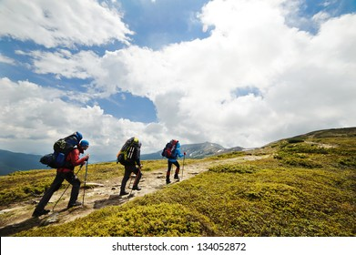 A group of people with backpacks walking along the road. There are mountains on the horizon. The sky is blue and cloudy.