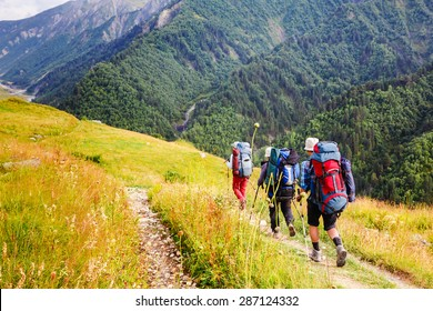 group of people with backpacks walking on the trail