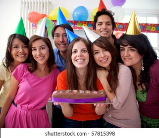 Group of people at a birthday party having fun and holding the cake