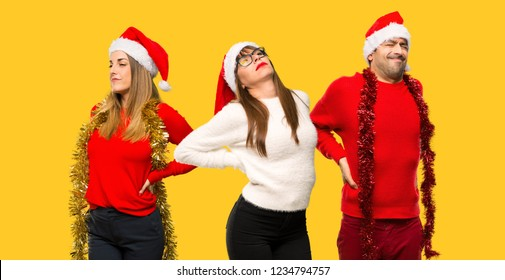 A group of people Blonde woman dressed up for christmas holidays suffering from backache for having made an effort on yellow background