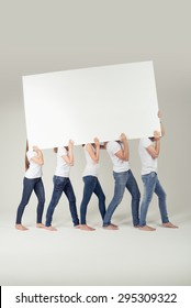 Group of People in Casual Outfits Carrying Empty White Large Board Over their Shoulders, Emphasizing Copy Space. Captured in Studio.