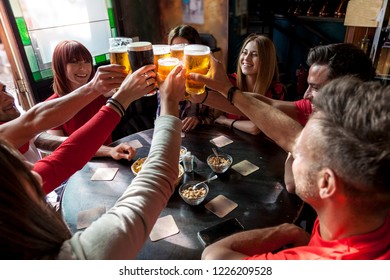 group of people celebrating in a pub drinking beer and eating snacks