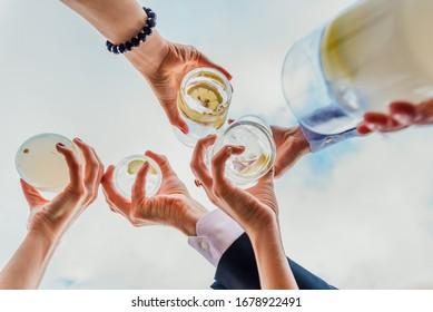 Grupo de personas celebrando un éxito con bebidas que ofrecen sus bebidas.