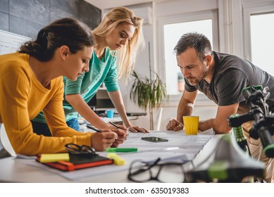 Group of people checking blueprints in the office