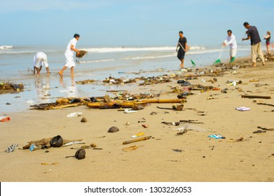 Group of people cleaning up beach from the garbage and plastic waste.