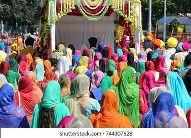 group of people with colorful clothes and women with veil in the head during the religious sikh event in the streets of the city