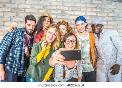 Group of people with colorful trendy clothes bonding together and having fun - Young cheerful friends taking a selfie