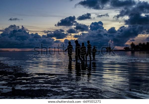 A group of people crosses the lagoon at Tarawa, Kiribati at dusk