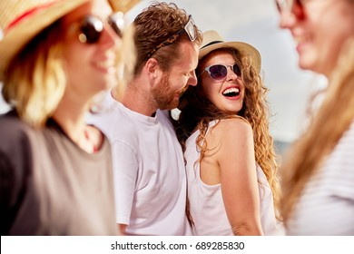 Group of people dancing, chatting and having a good time at beach party