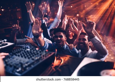 Group of people dancing in front of a DJ
