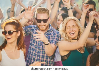 Group of people dancing at summer festival, hands raised