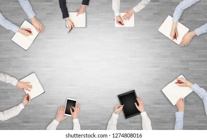 Group of people with devices in hands having desk discussion and making reports together on laptop, tablet, notebook