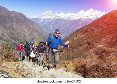 Group of People of different age and ethnicity walking up on Mountain Trail during Hike in Nepalese Himalaya carrying heavy backpacks and climbing gear led by mature Guide Sun shining
