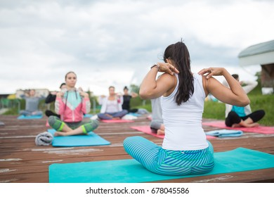 Group of people of different age yoga exercise in the park at summer. Big group of adults woman doing yoga class outdoor in nature