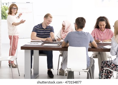 Group of people of different nationalities sitting beside desk in light classroom, in the background mature teacher