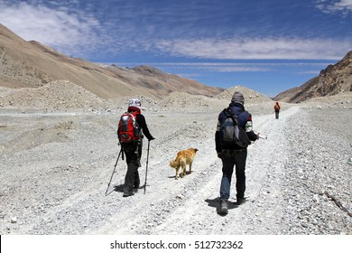 A group of people and a dog hike along a dirt road under a group of prayer flags in the arid and desolate Rongbuk valley near Mount Everest in the Himalayas, Tibet.