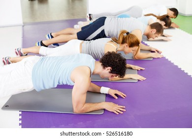 Group of people doing abdominal exercise in the gym, based on elbows and lifting their bodies.