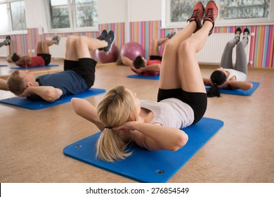 Group of people doing crunches on exercise floor mat