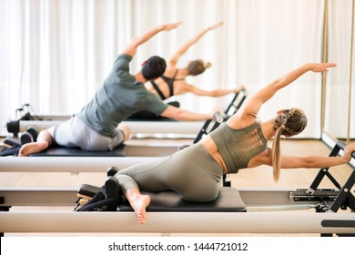 Group of people doing the mermaid pilates exercise or side stretch to tone the intercostal muscles viewed from the rear