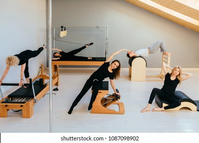 Group of f??? people doing pilates exercises with chair, barrel, spine corrector, reformer, cadillac - different equipment in modern eco studio interior.