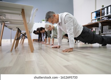 Group Of People Doing Pushups Exercise At Workplace