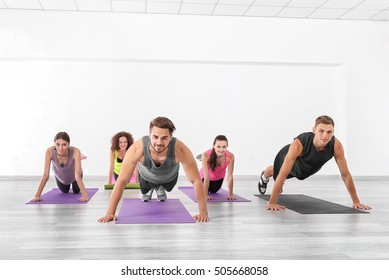 Group of people doing push-ups in yoga class