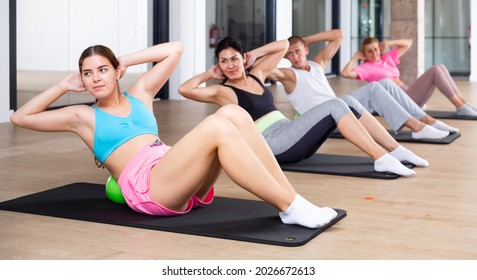 Group of people doing spine twist exercise with small pilates ball under their backs