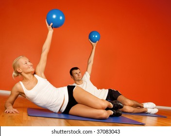 Group of people doing stretching exercise with fitness balls in fitness room