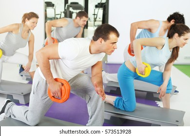 Group of people doing triceps exercise with weights in weight training class with instructor in front.  Selective focus on the trainer.
