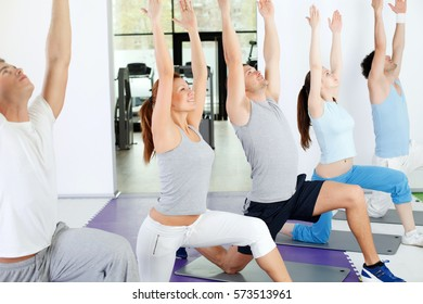 Group of people doing yoga exercise at yoga training class.