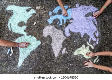A group of people drawing with colored chalks on the floor with his hands in the street a map of the world