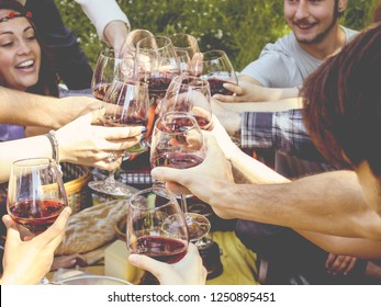 group of people drinking wine toasting together. close up crop on red wine glasses clinking together outdoors.