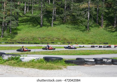 Group of people driving go-kart car at outdoor playground