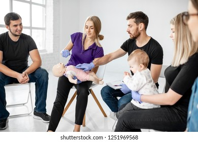 Group of people during the first aid training with instructor showing on manikin how to do artificial respiration for the baby