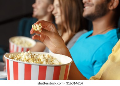 Group of people eating popcorn in the cinema